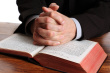 ist1_11592620-praying-hands-on-an-open-bible.jpg